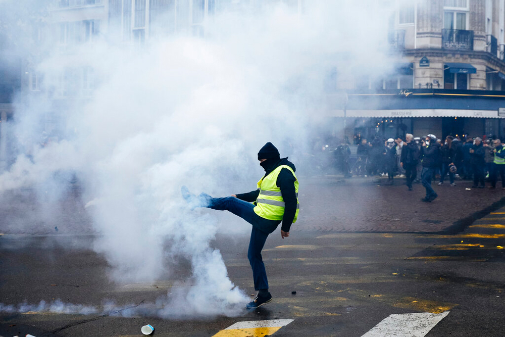 A protester kicks away a tear gas canister during a Yellow Vest demonstration in Paris on November 16, 2019