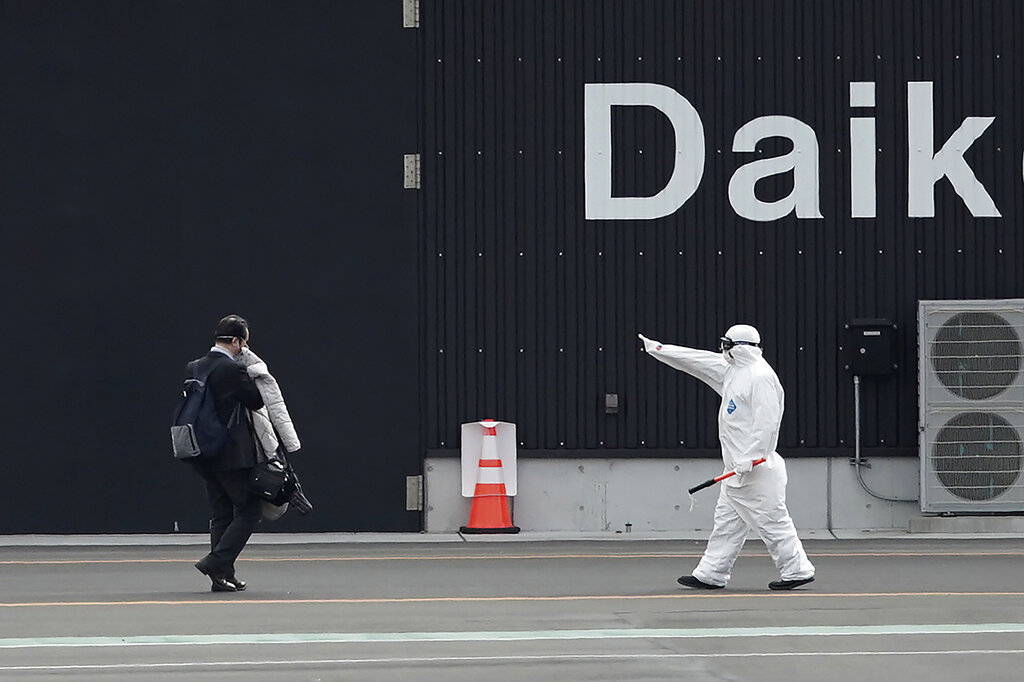 One of passengers, left, from the quarantined Diamond Princess cruise ship is guided after walking out from the ship at a port in Yokohama, near Tokyo, Wednesday