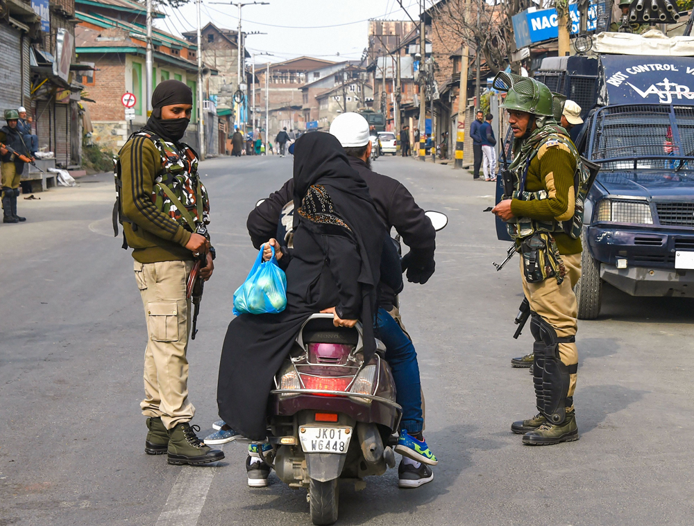 Security personnel ask a scooterist to divert his route during restrictions in parts of Srinagar on Friday, November 1, 2019.