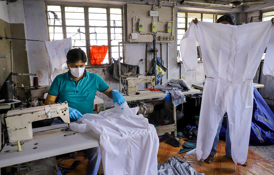 Workers stitch preventive suits at a workshop the view of the coronavirus pandemic, in Howrah on Saturday