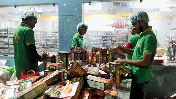 Labourers pack cakes for Christmas at a bakery in Bandel