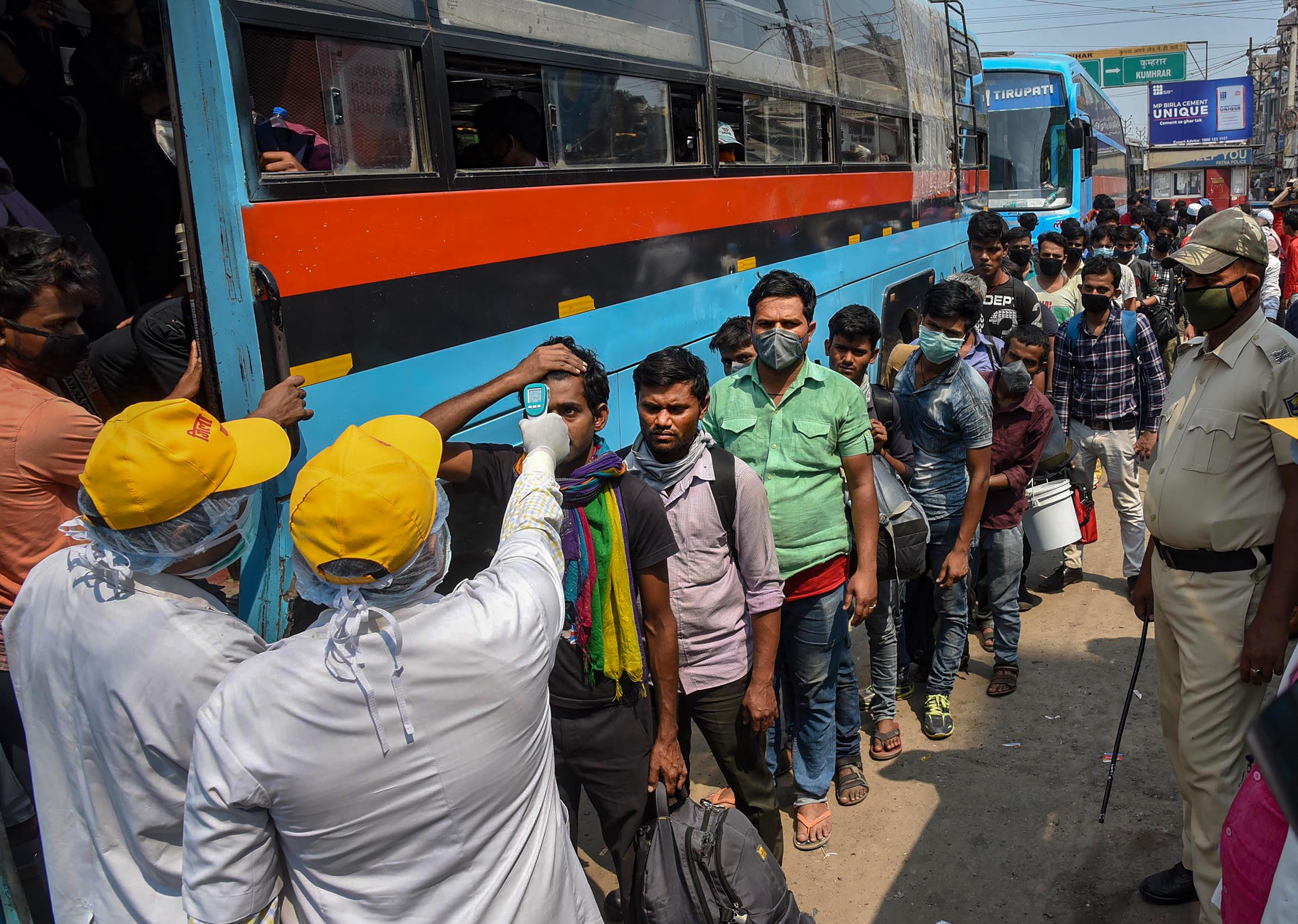 Passengers board a crowded bus during Janata curfew in the wake of coronavirus pandemic, in Patna, Sunday, March 22, 2020