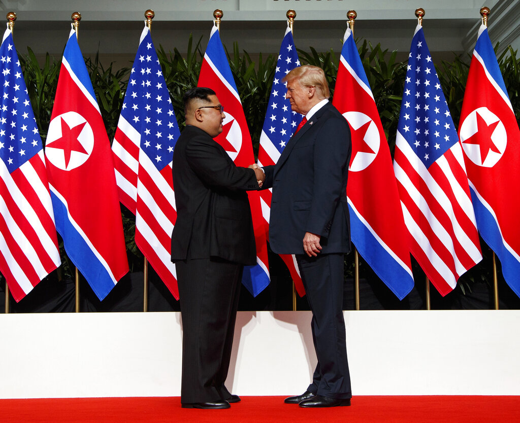 Kim Jong-un and Donald Trump shake hands before their meeting on Sentosa Island in Singapore on June 12, 2018.