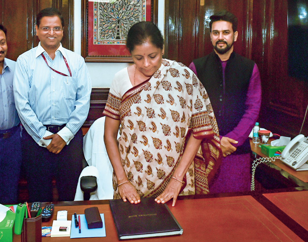 Nirmala Sitharaman touches her file out of reverence as she takes charge of the finance ministry in New Delhi on Friday.