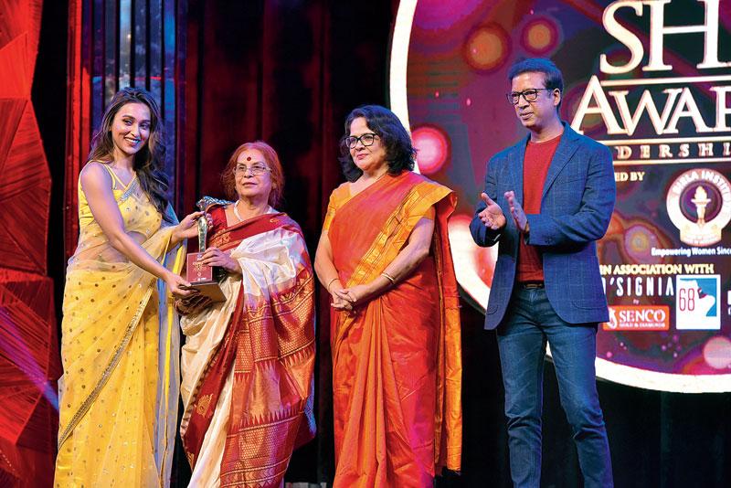 Bani Basu receives her award from Mimi Chakraborty, Sanjukta Bose and Namit Bajoria, founder Kutchina.