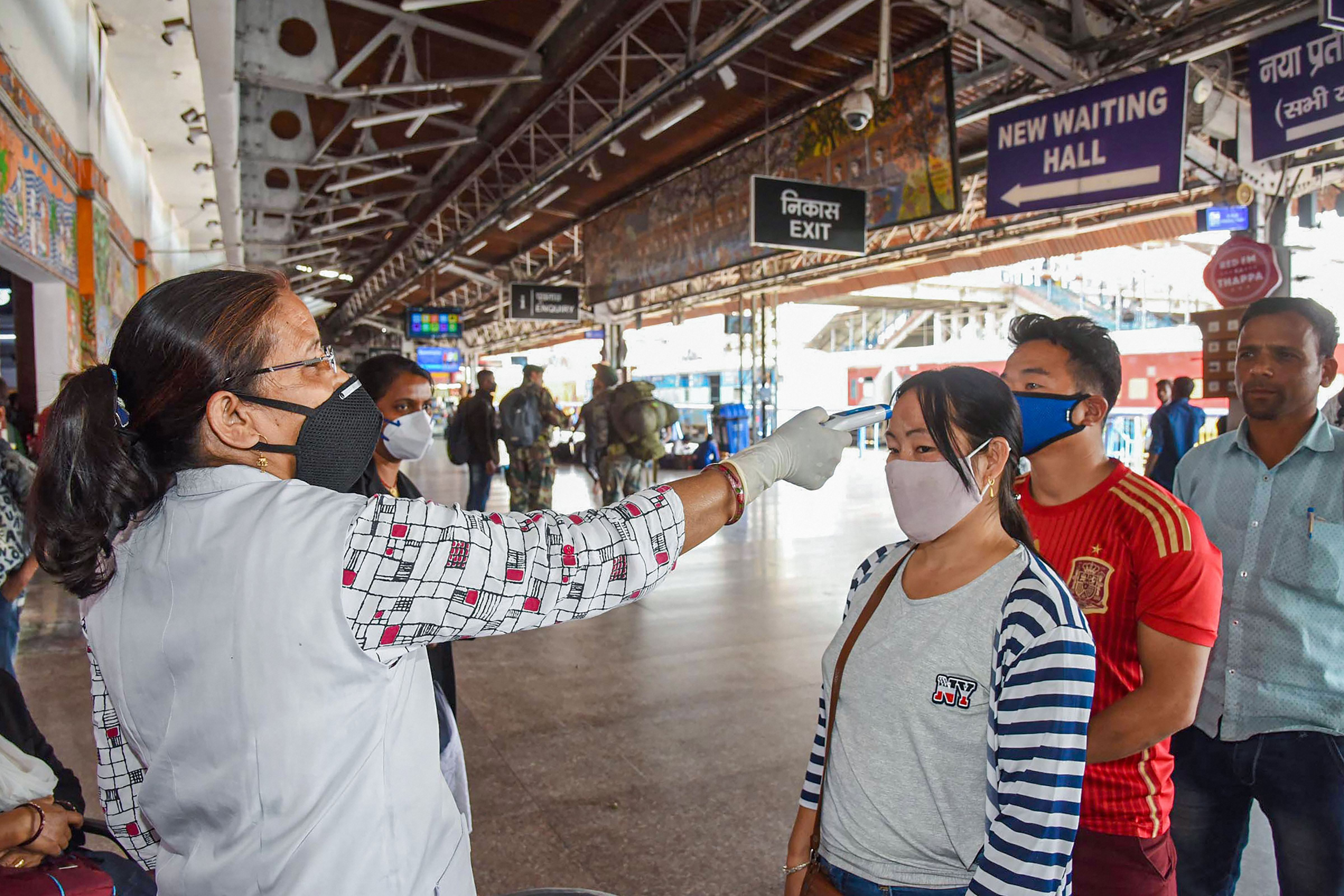 A health worker uses a thermal screening device on travellers in the wake of coronavirus pandemic, at Patna junction, Friday, March 20, 2020