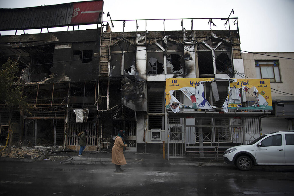 In this photo taken Monday, Nov. 18, 2019, and released by Iranian Students' News Agency, people walk past buildings which burned during protests that followed the authorities' decision to raise gasoline prices, in the city of Karaj, Iran. An article published Tuesday in the Keyhan hard-line newspaper in Iran is suggesting that those who led violent protests will be executed by hanging as the unrest continues.