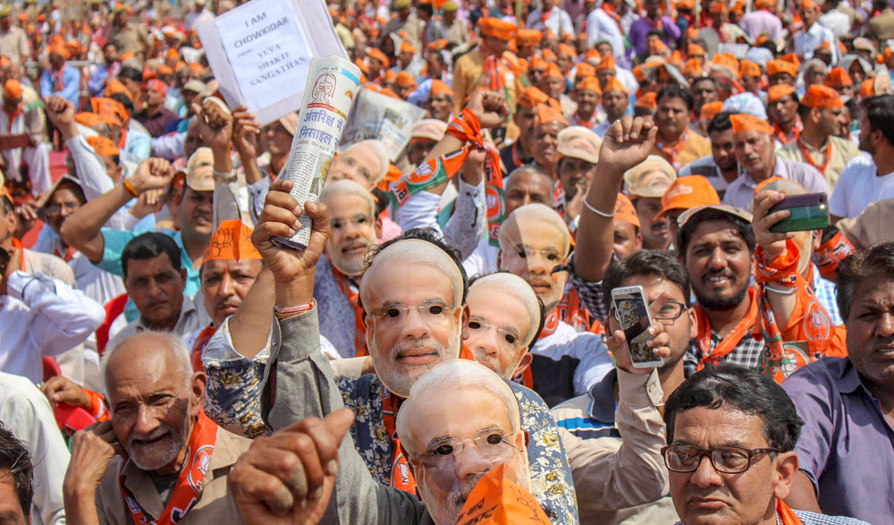 BJP workers wear masks of Narendra Modi at the campaign rally in Meerut on Thursday