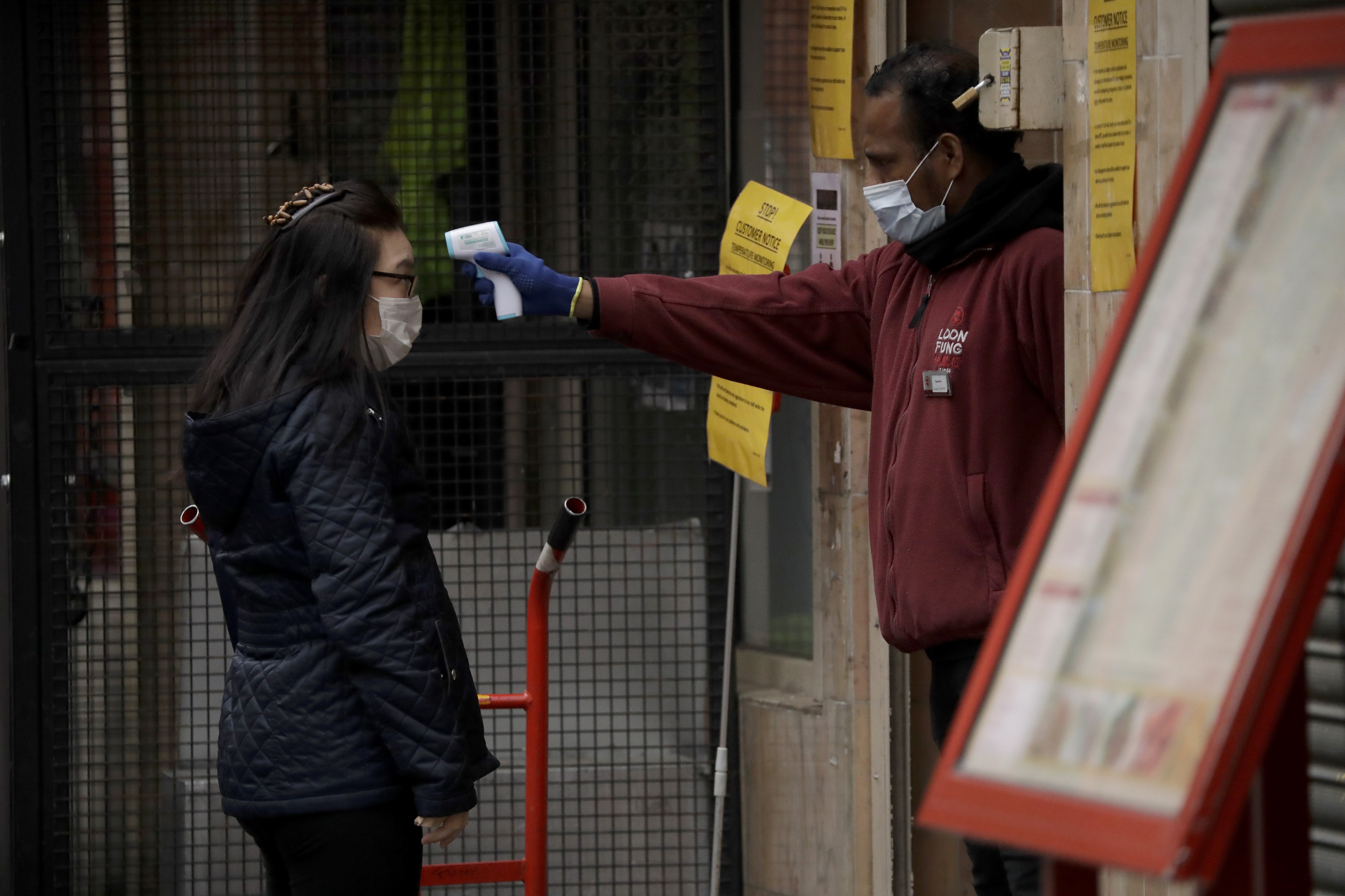 A customer has temperature taken before entering the Loon Fung Chinese supermarket on Gerrard Street