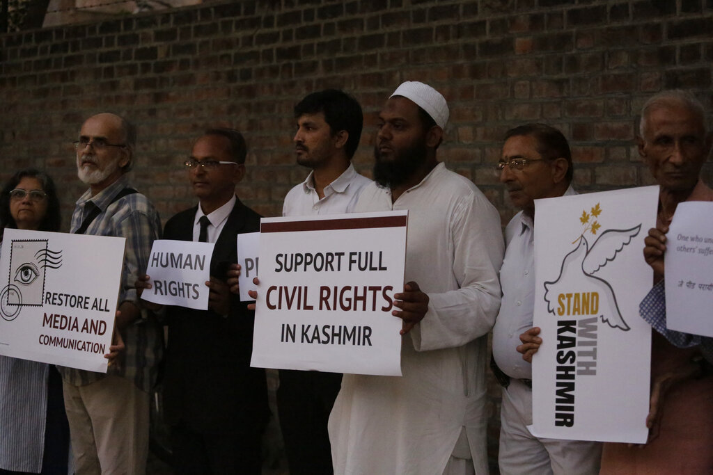 In this Tuesday, October 17, 2019, file photo, people hold placards calling for peace in Kashmir and expressing solidarity with its citizens in Ahmadabad.