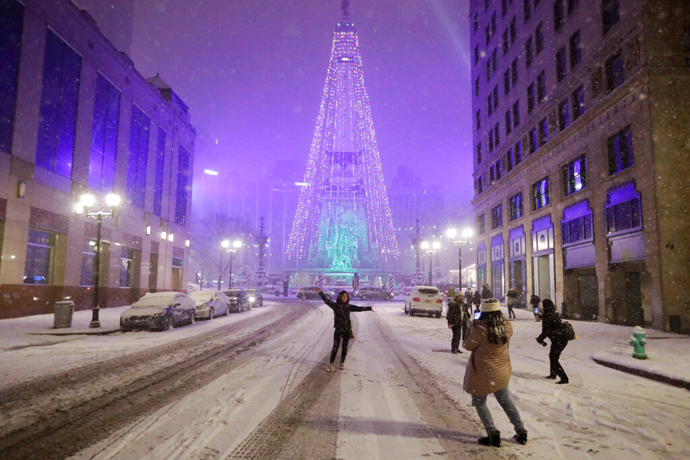 Local residents pose for photos as snow falls in Indianapolis on December 15
