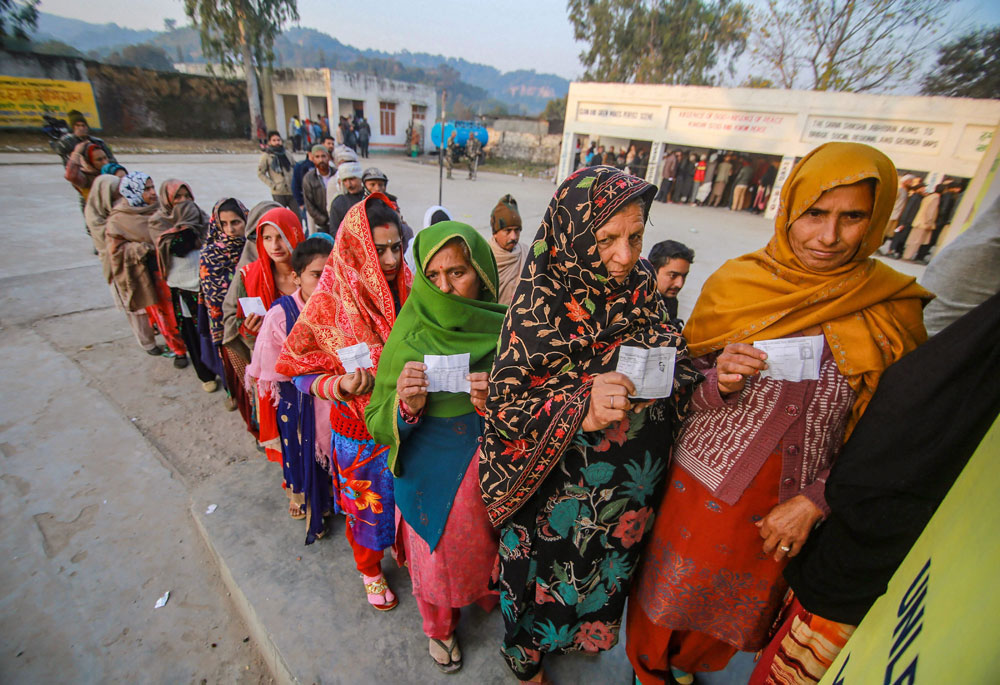 Voters stand in a queue to cast their votes in the 8th phase of panchayat elections in Jammu on Saturday, December 8, 2018.