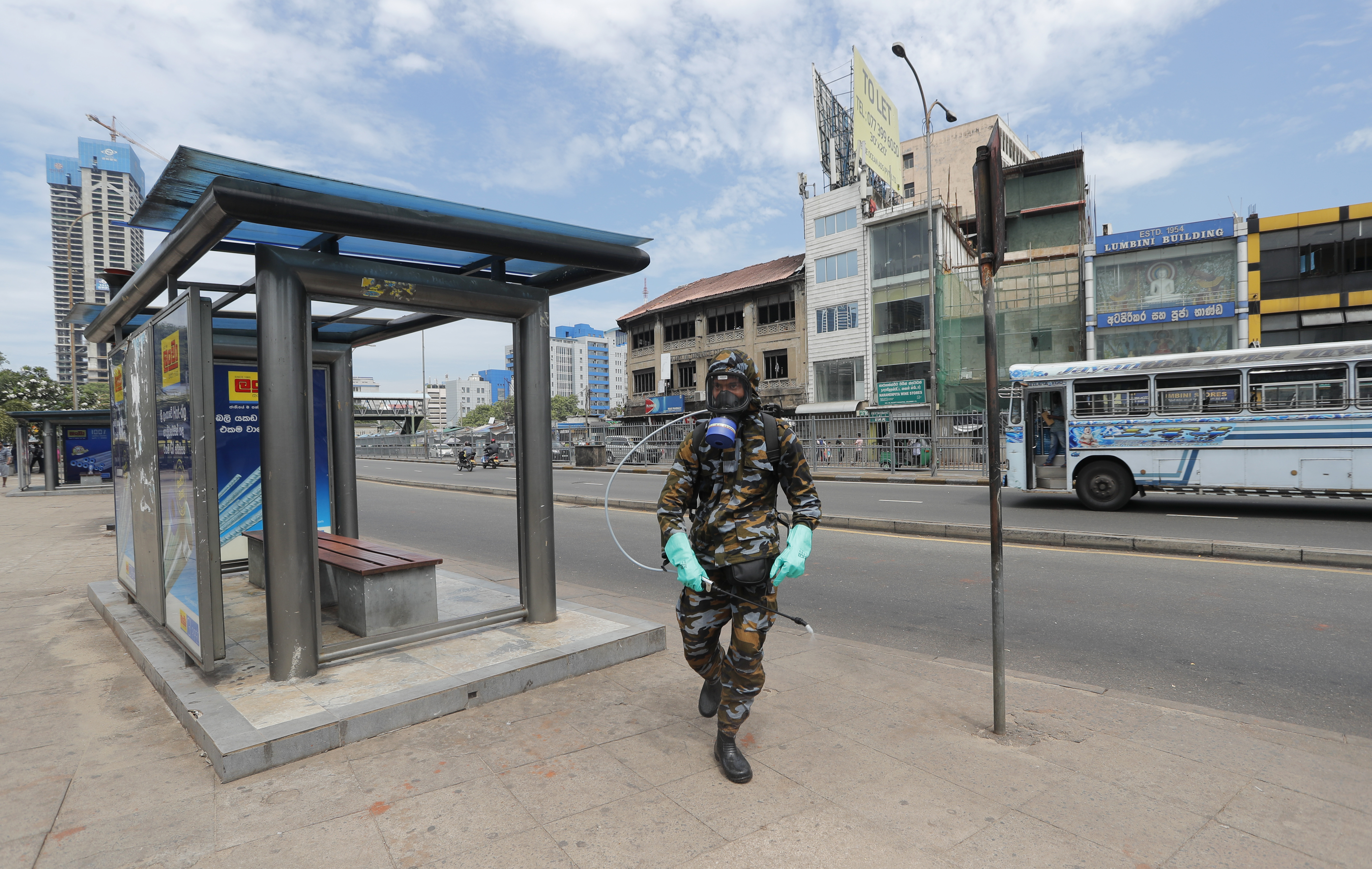 A Sri Lankan government soldier in protective clothes sprayS disinfectants at a bus stop in Colombo, Sri Lanka on Wednesday