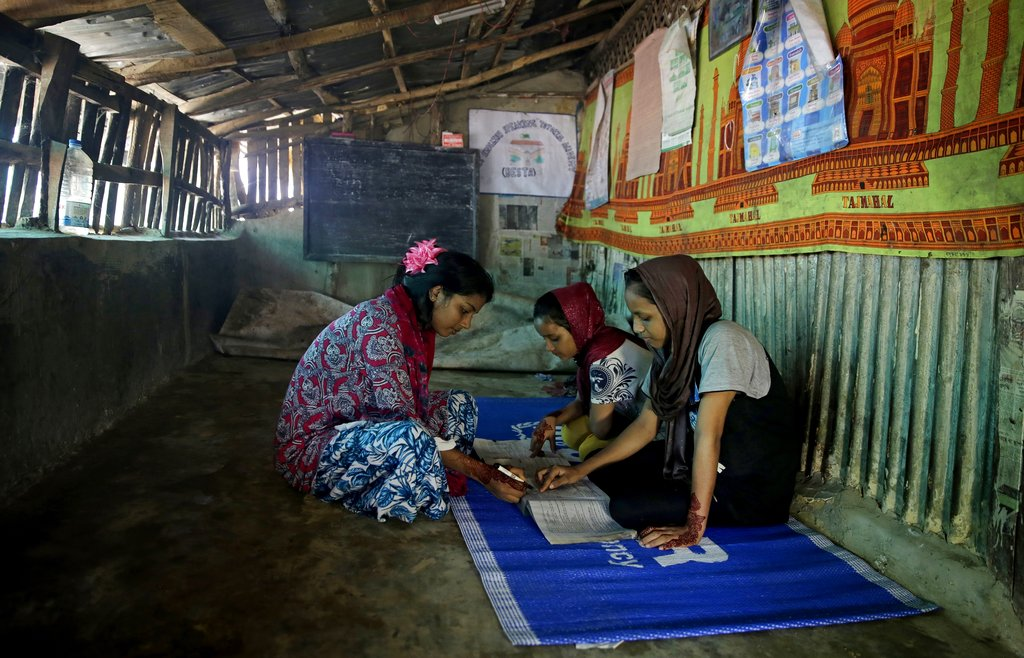 Rahima Akter  teaches her siblings inside the family hut at the Kutupalong refugee camp.