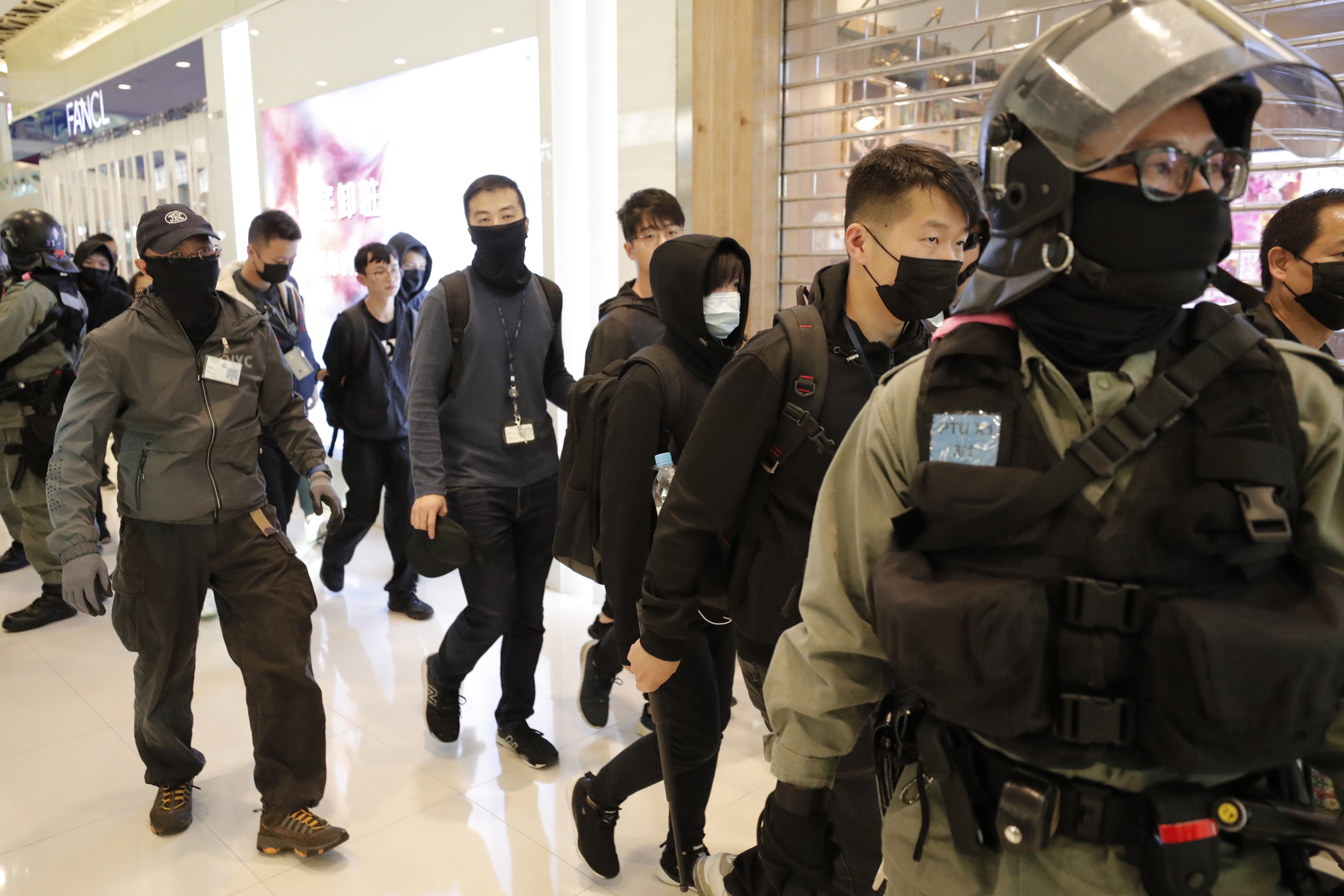 Policemen detain protesters at a shopping mall popular with traders from mainland China near the Chinese border in Hong Kong, Saturday, December 28, 2019