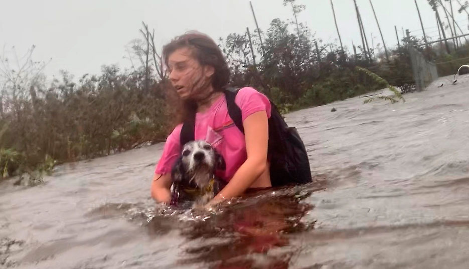 Julia Aylen wades through waist deep water carrying her pet dog as she is rescued from her flooded home during Hurricane Dorian in Freeport, Bahamas, on September 3, 2019.