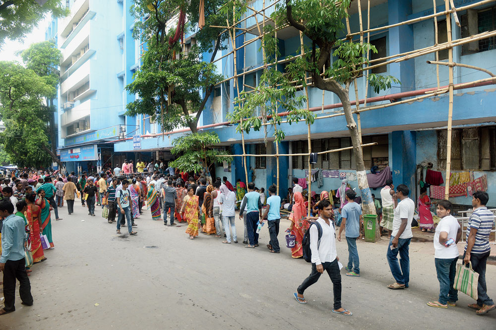 Visitors, some with food packets and water for patients undergoing treatment, queue up to enter the UNB Building of NRS hospital where the trouble had started after the death of a 75-year-old patient on Monday. Usually visitors have free access to the building as they come to deliver food and water for patients in the afternoon, on Wednesday security was tightened and only those having visitor's pass were allowed in.