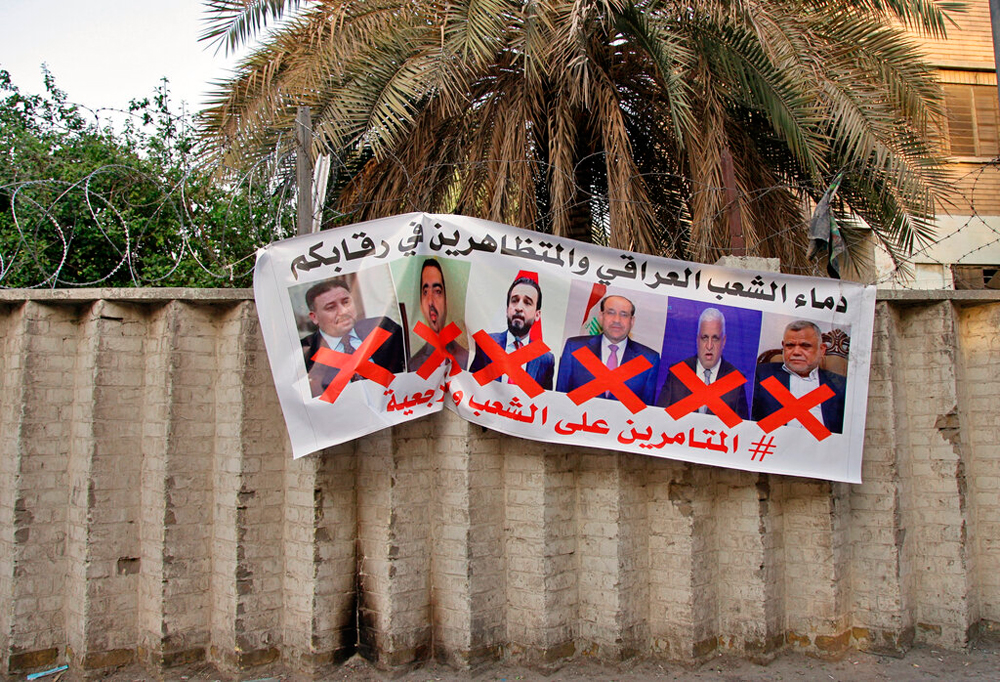 A poster with defaced pictures of Iraqi politicians and Arabic text that reads: