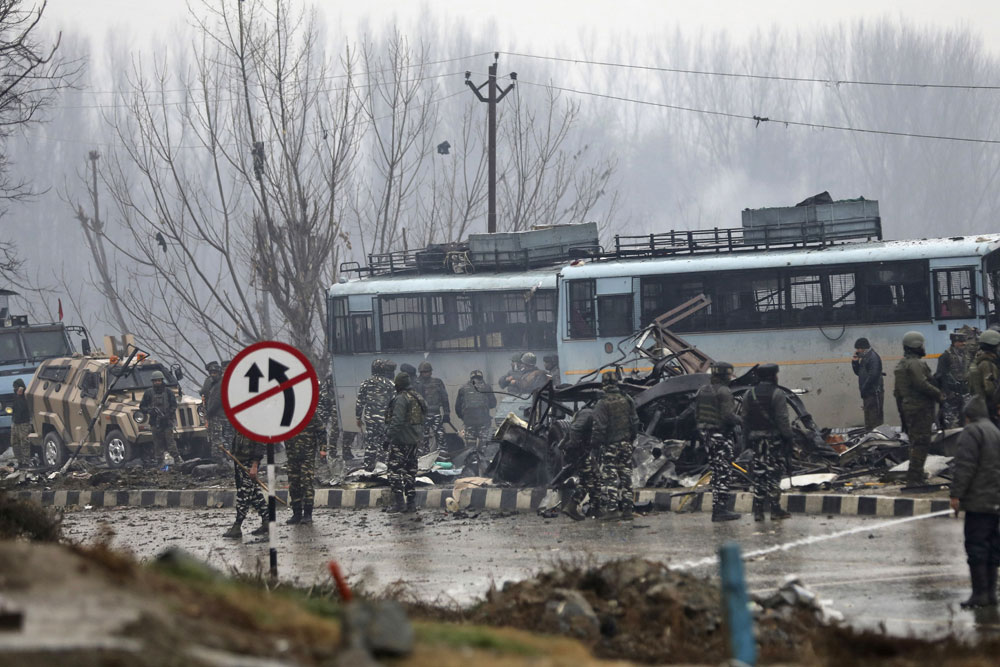 Indian paramilitary soldiers stand by the wreckage of a bus after the suicide bomb explosion in Pulwama.