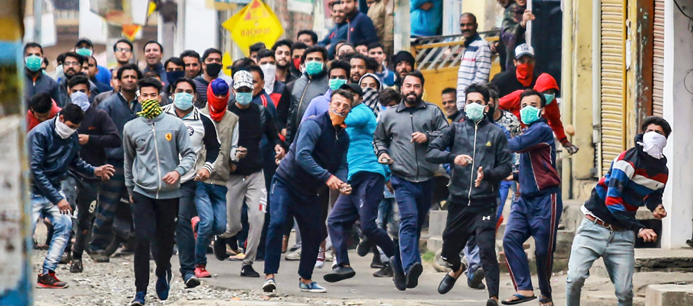 Protestors clash with police personnel during a curfew, imposed on the third day after the clash between two communities over the protest against the Pulwama terror attack, in Jammu, on Sunday.