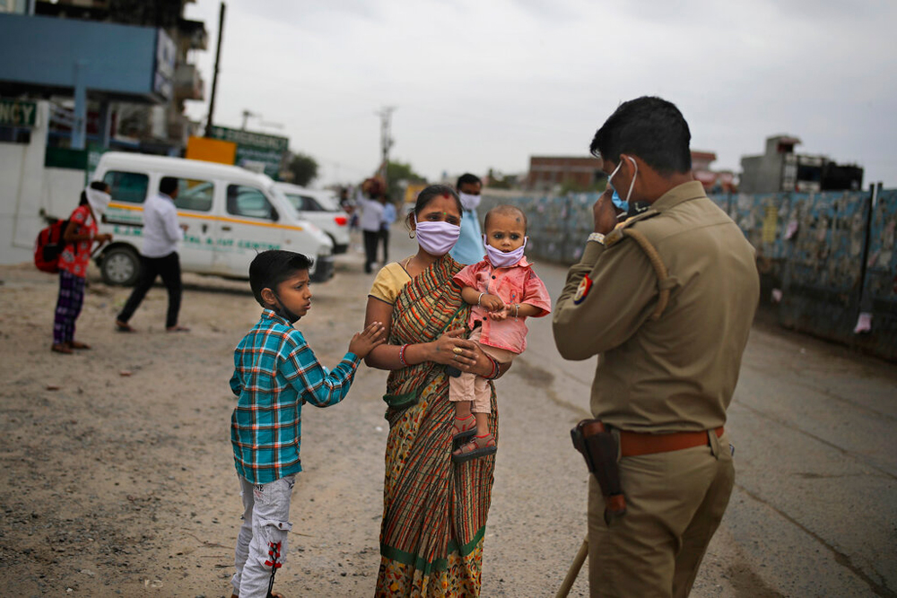A woman pleads before a policeman to let her pass a check point hoping to walk to her home with her family on the outskirts of New Delhi on Thursday