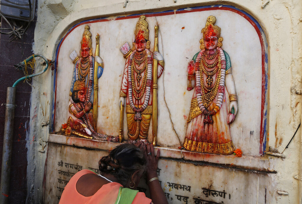 A Hindu pilgrim touches in obeisance an image of Hindu deities Rama, Sita and Lakshman in Ayodhya, on Saturday, Nov. 9, 2019.