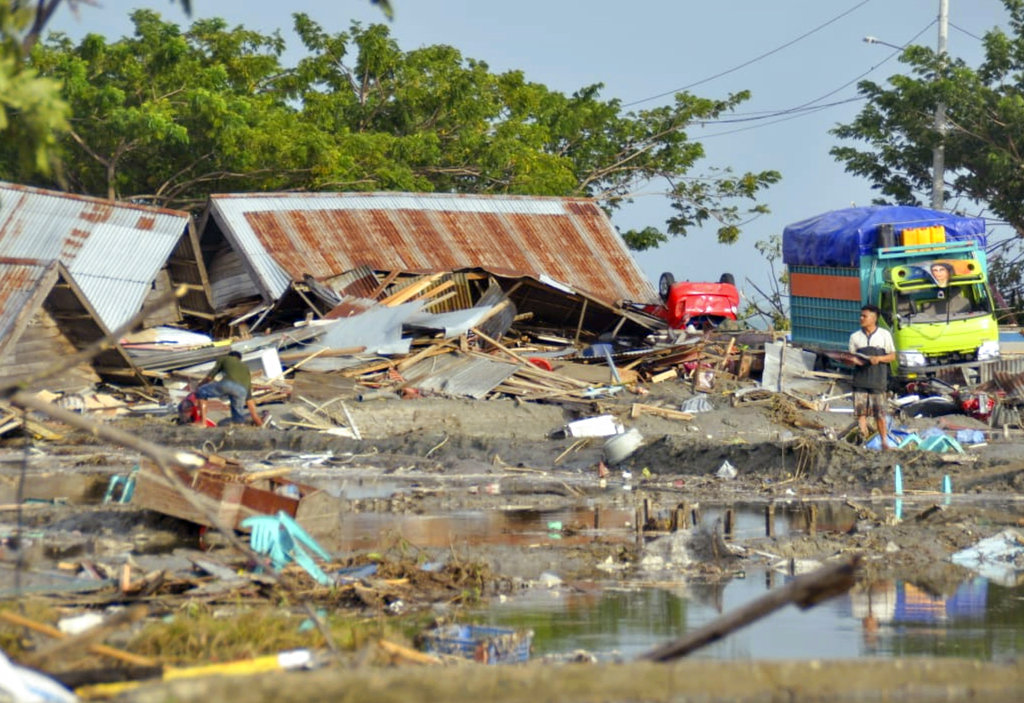 A man stands amid the damage caused by a tsunami in Palu, Indonesia on Saturday.