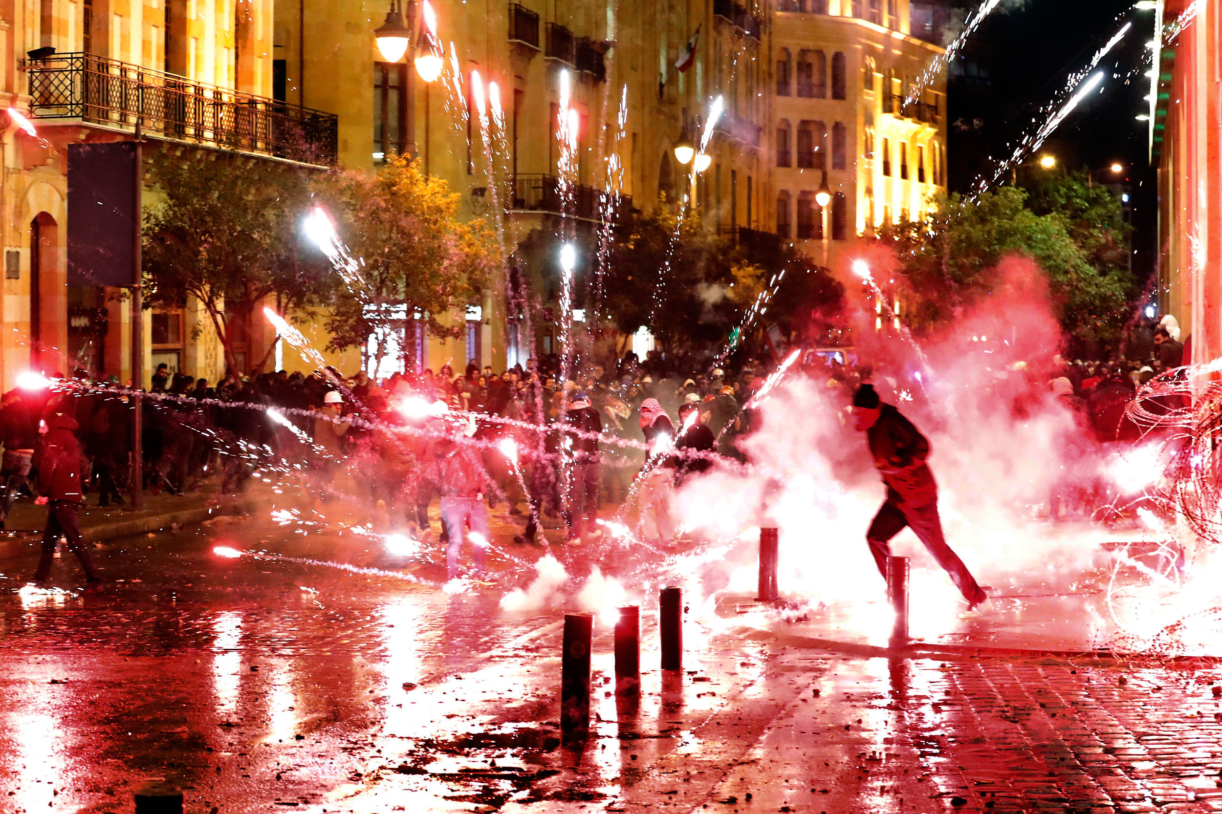 Anti-government protesters throw firecrackers at riot police during a demonstration against the new government, near Parliament Square, in Beirut, on Wednesday.