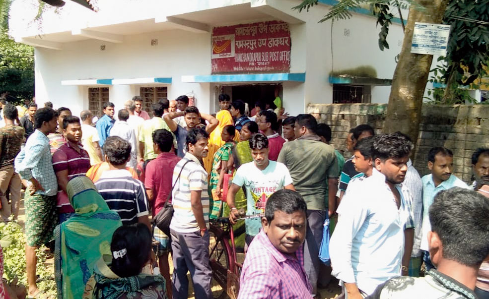 Customers agitate in front of the Ramchandrapur sub-post office in Moyna.