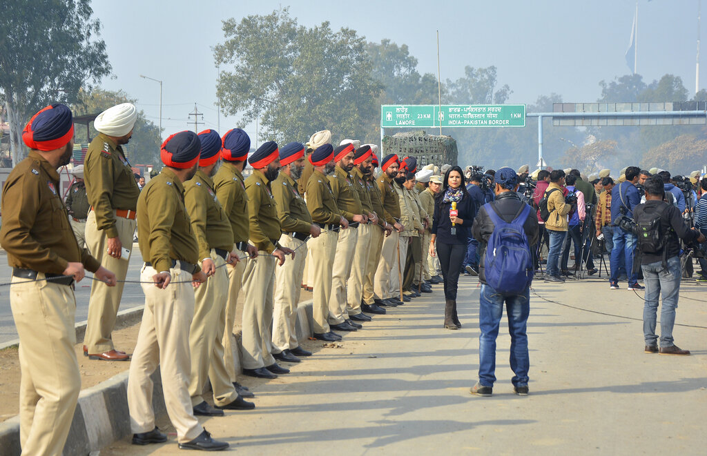 Indian policemen and reporters wait for the return of Wing Commander Abhinandan Varthaman at Wagah on Friday.