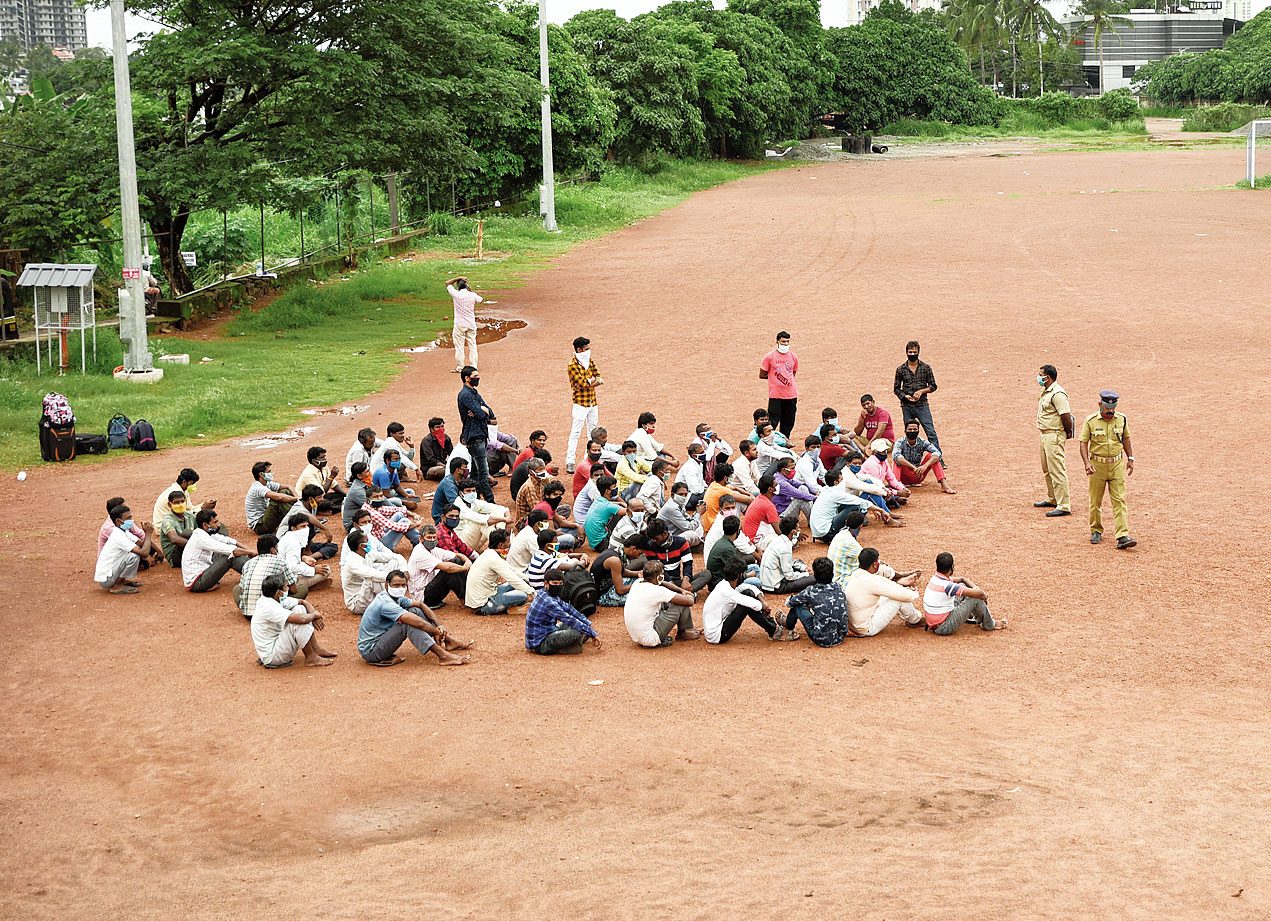 Migrant workers wait for buses to catch a home-bound train from Kerala earlier this month.