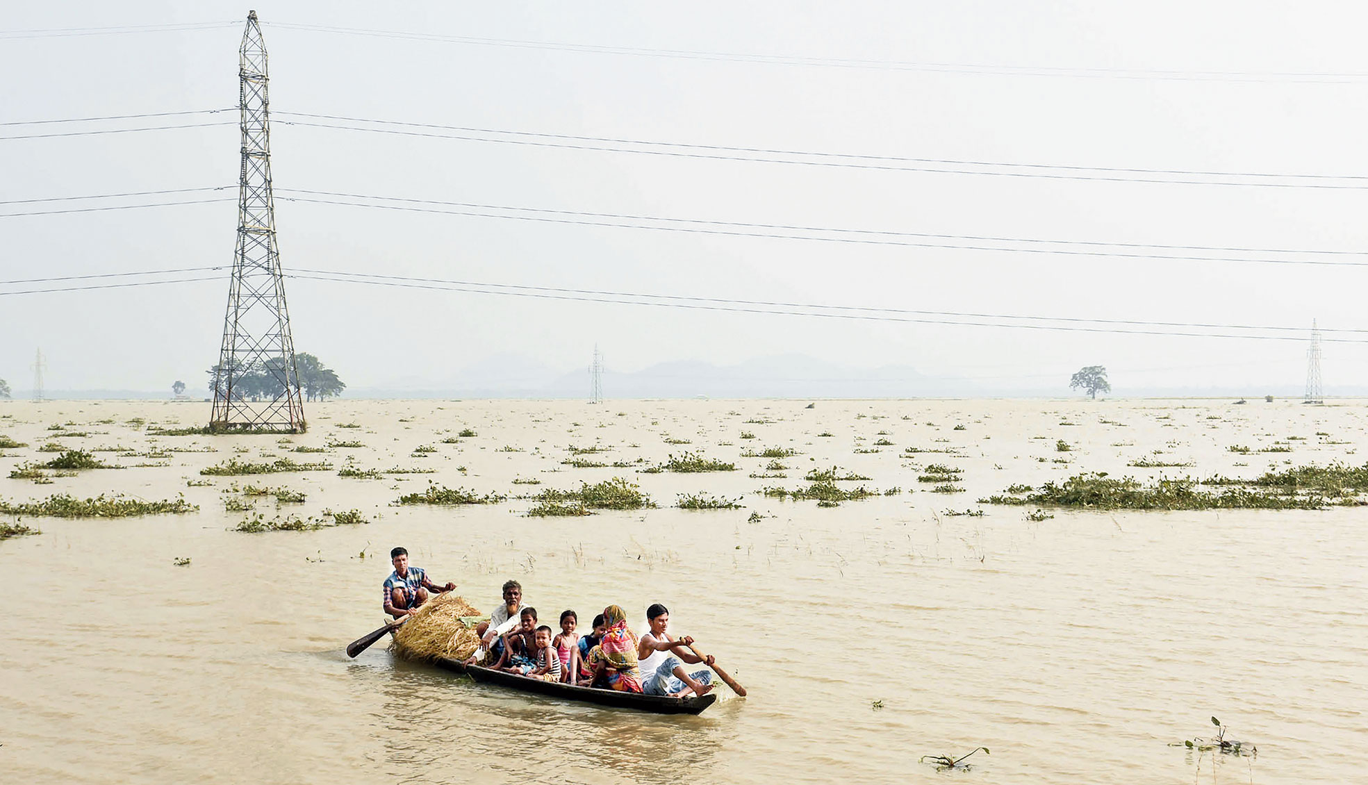 People shift to a safer place on a boat in flood-affected Morigaon district of Assam.