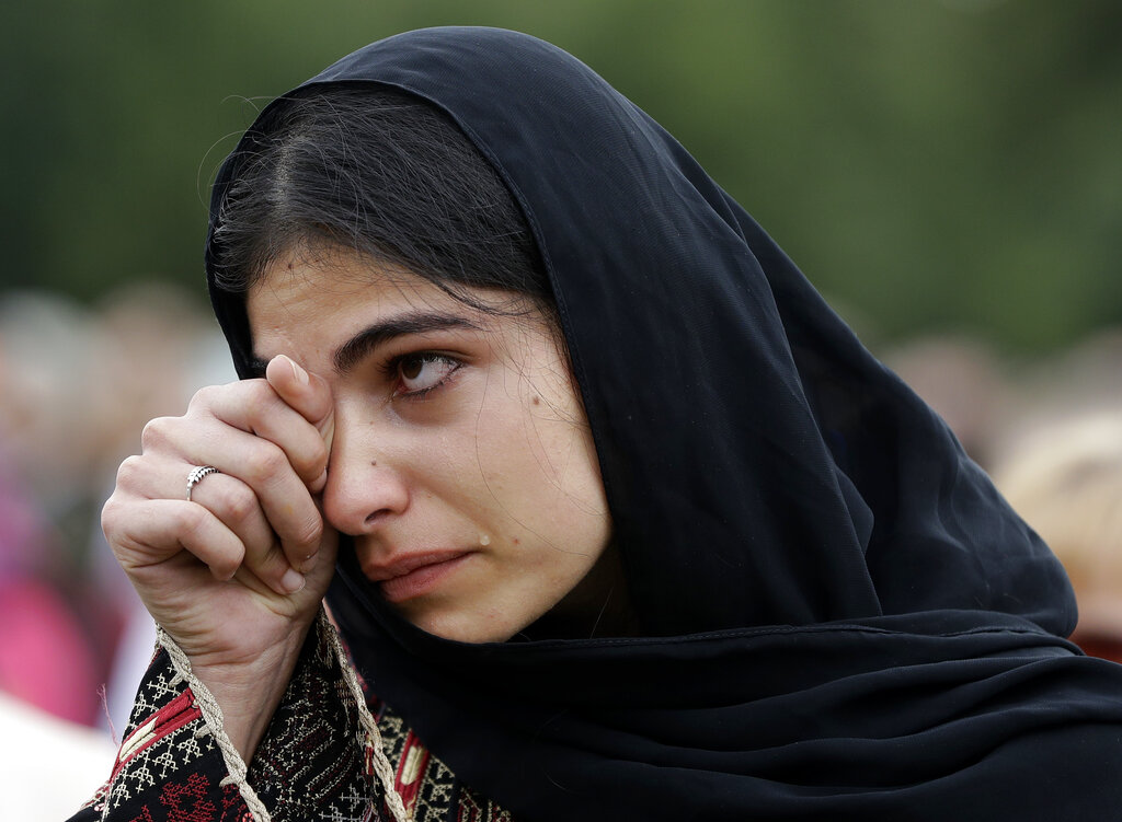 A young Muslim woman wipes tears from her face during the March for Love in Hagley Park.
