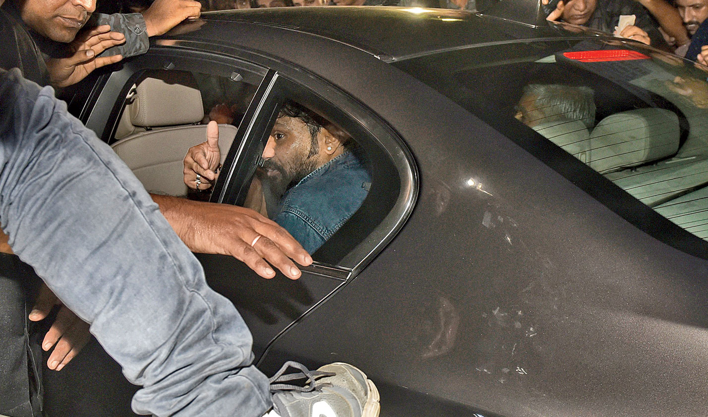 A man's foot is seen on governor Jagdeep Dhankhar's car as he and Union minister Babul Supriyo try to leave Jadavpur University