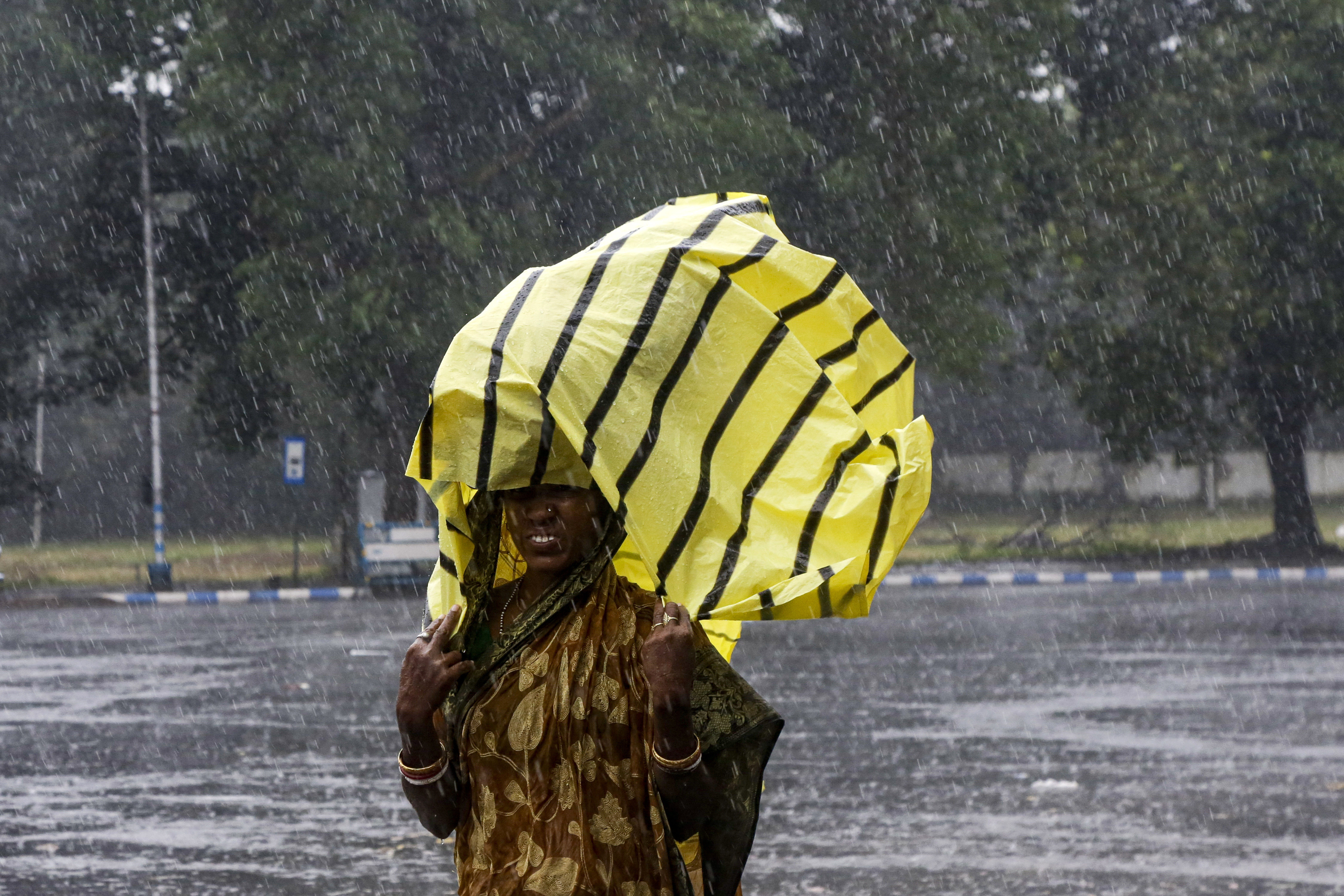 A woman covers her head with a plastic sheet as it rains in Kolkata, India, Saturday, November 9, 2019