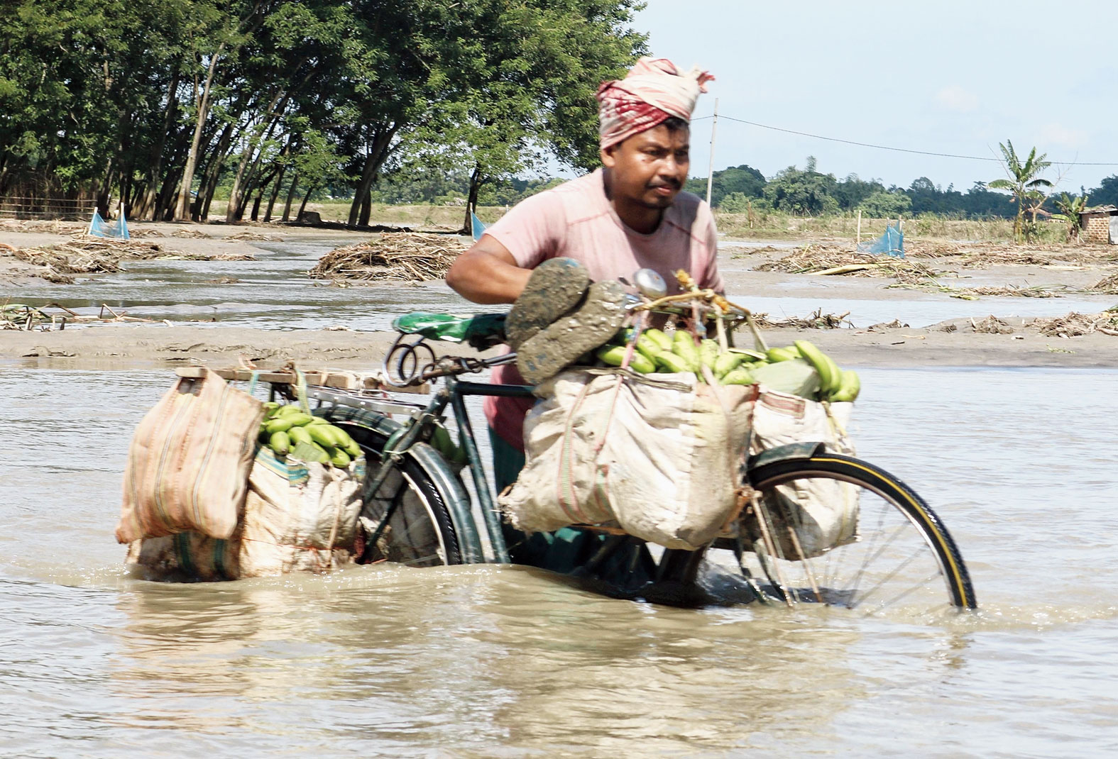 A man manoeuvres his loaded bicycle through a flooded stretch on the Tamulpur to Dhamdhama road near the Pagladiya in Baksa.