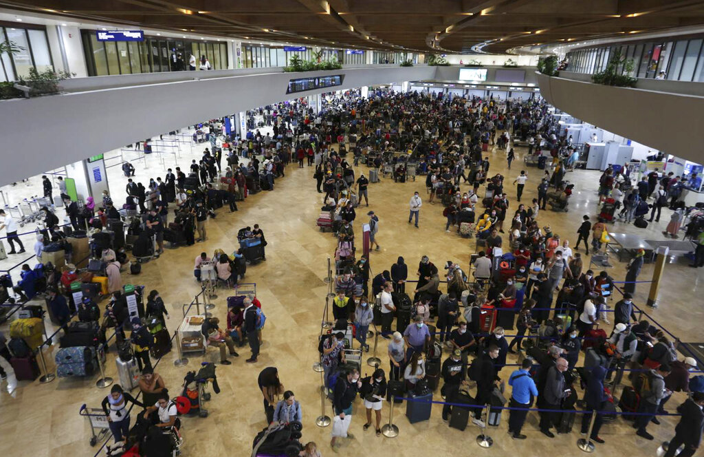 In this handout photo provided by the Manila International Airport Authority (MIAA) Media Affairs, passengers wait for their flight at the departure area of Manila's International Airport, Philippines on Tuesday, March 17, 2020.