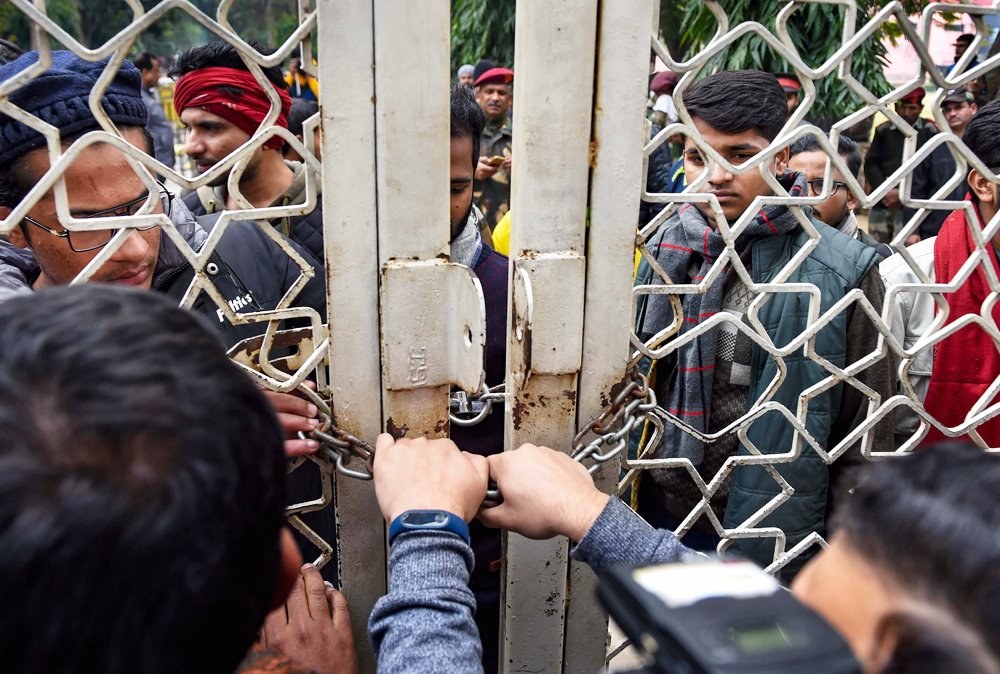 Jamia Milia Islamia University students attempt to break a lock during a protest against their Vice Chancellor Najma Akhtar, demanding registration of an FIR against Delhi Police in connection with last months violence inside the campus, in New Delhi, Monday, January 13, 2020.