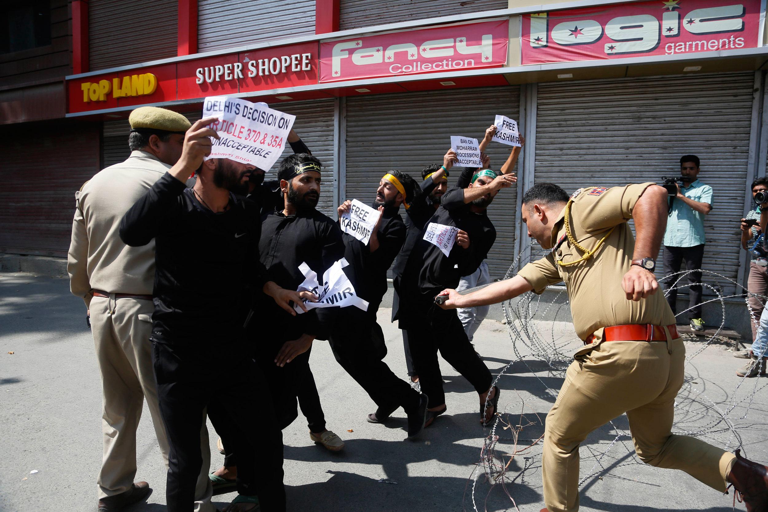 "A policeman thrashes Kashmiris during a procession in Srinagar last Sunday. Earlier last week, the Shri Lal Bahadur Shastri Rashtriya Sanskrit Vidyapeetha, Delhi, had organised a ""debate"" among non-teaching staff on the topic: ""Abrogation of 370 is in the national interest: For and Against""."