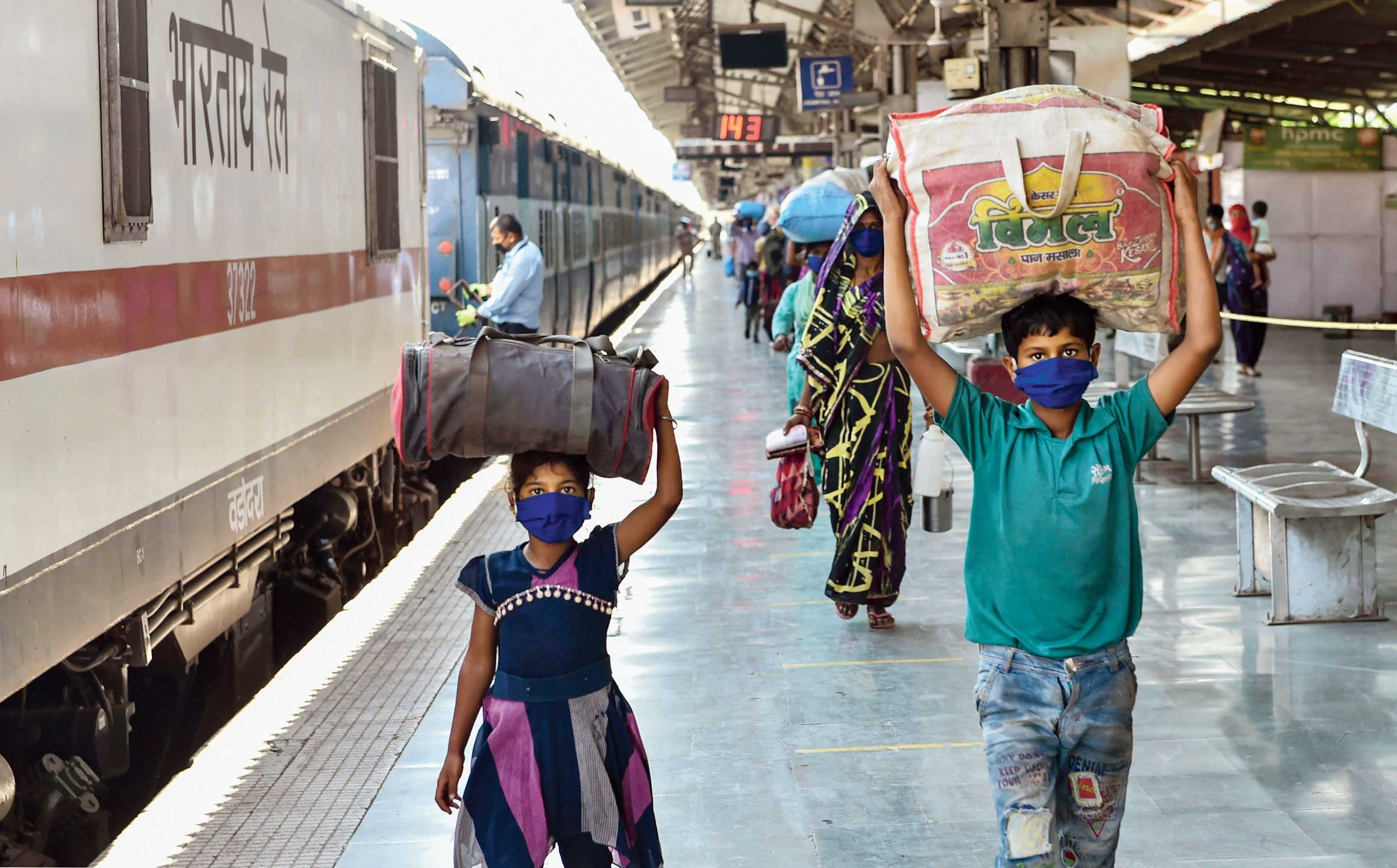 Migrant workers and their families make their way out of Charbagh station in Lucknow on Wednesday after arriving by a special train from Maharashtra.