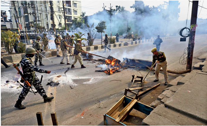 Burning logs being removed from a road in Guwahati on Thursday