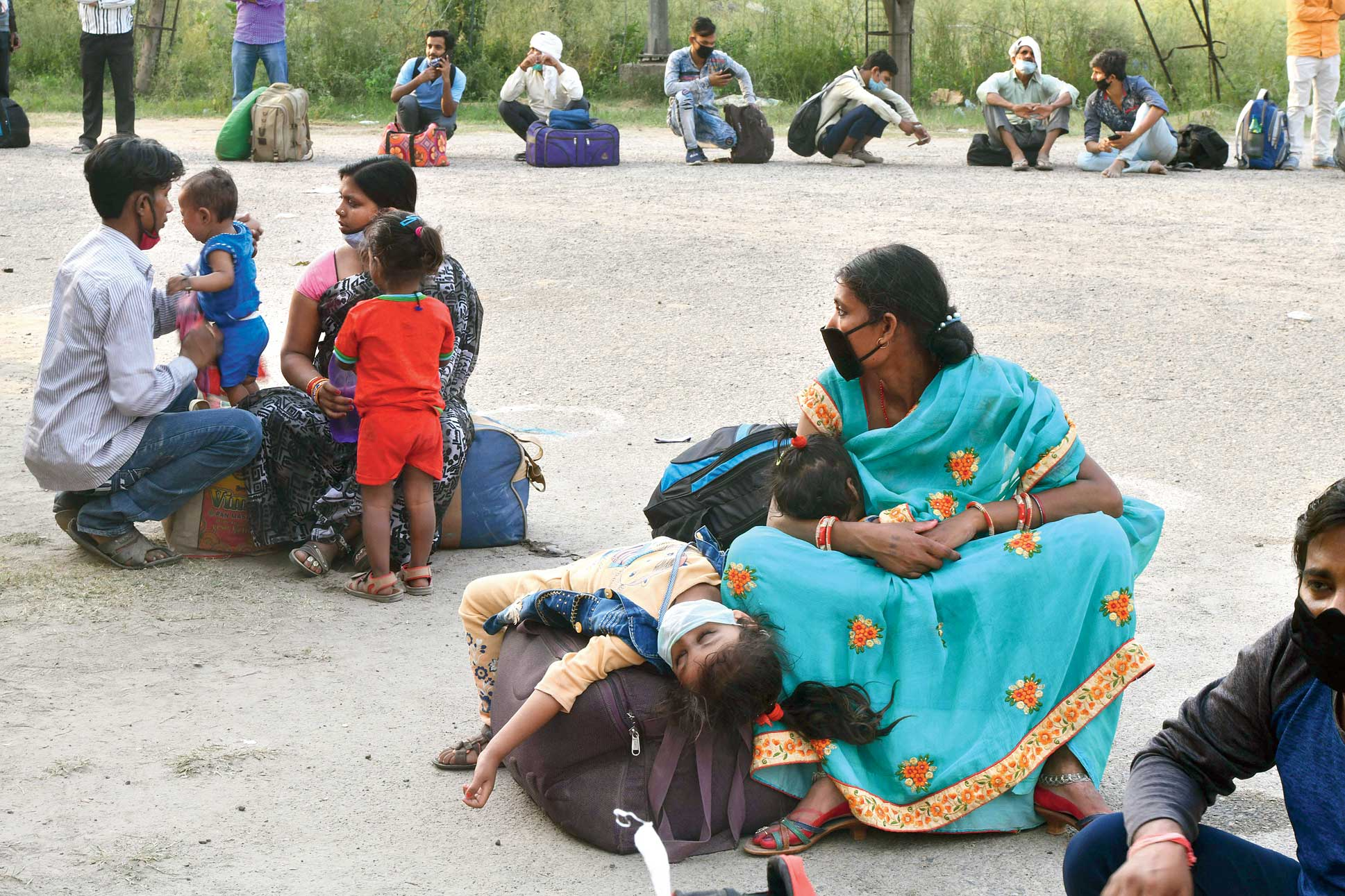 Migrants along with their children wait to board a bus in Noida on Tuesday to reach their home in Bihar.