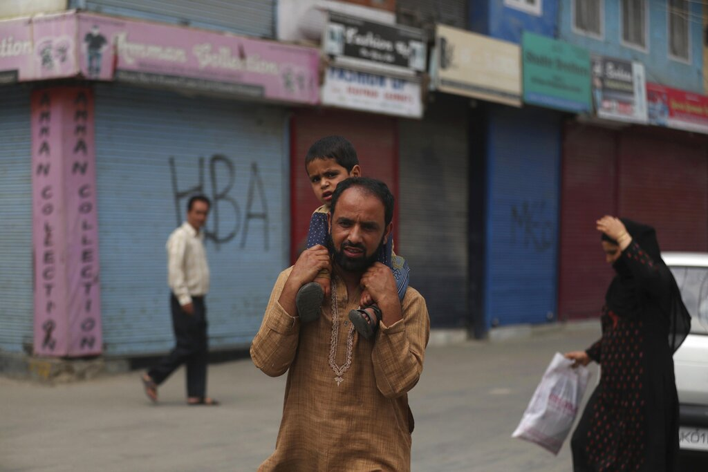 A Kashmiri man carries a child on his shoulders in a closed market area in Srinagar