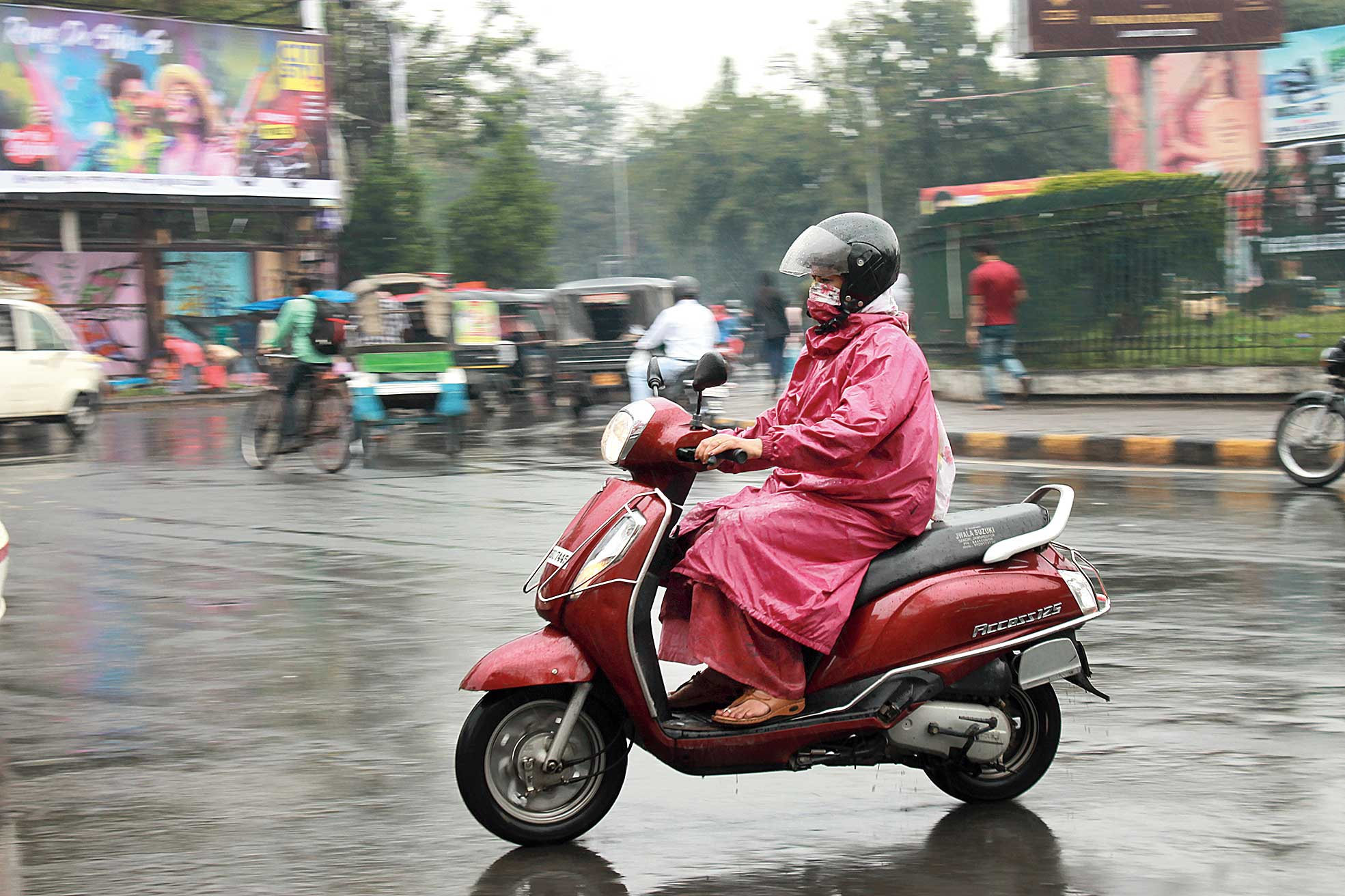 A woman rides a scooter in the rain in Sakchi, Jamshedpur, on Wednesday.
