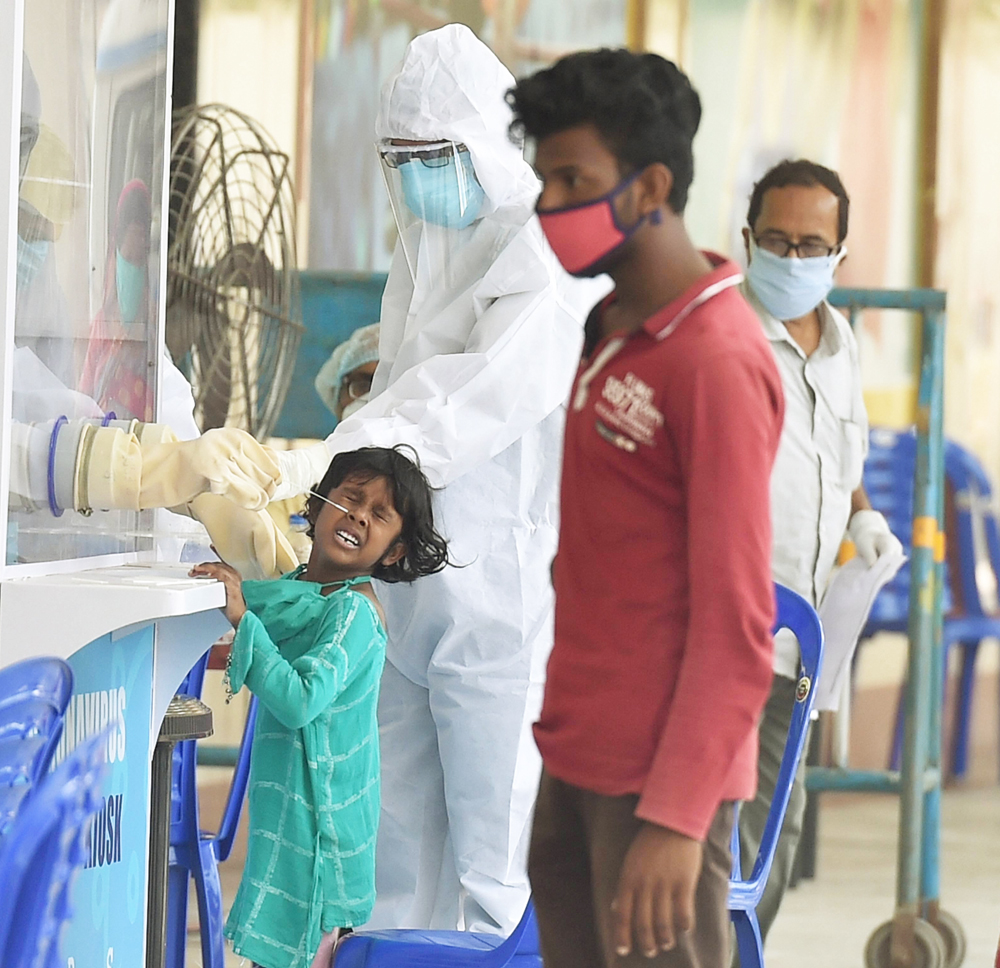 A girl reacts as a medic collects her swab sample for a Covid-19 test at a quarantine centre during the 3rd phase of the nationwide lockdown, in Howrah district of West Bengal, Wednesday, May 6, 2020.