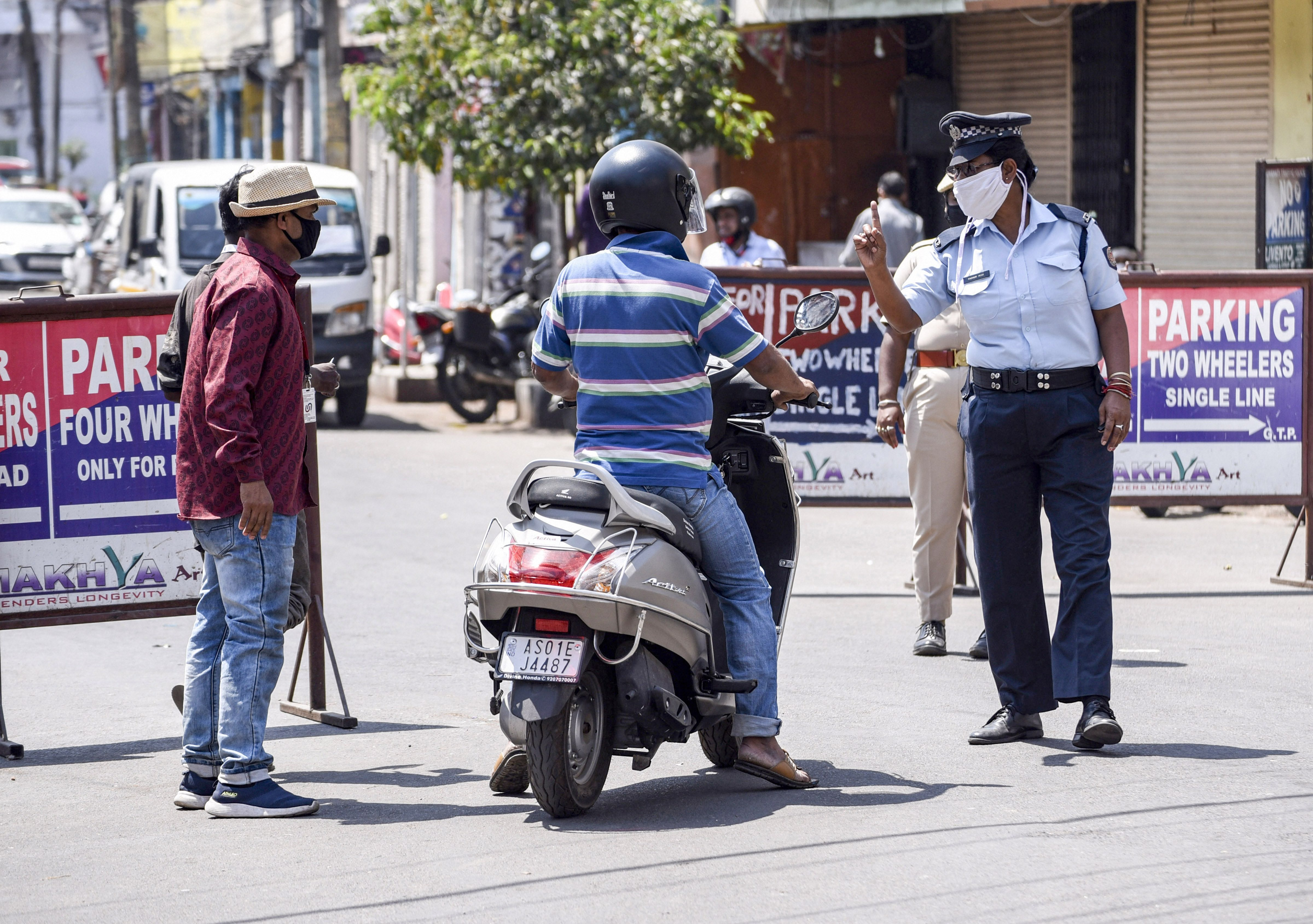 Security personnel stop commuters during a nationwide lockdown in the wake of coronavirus outbreak, in Guwahati, Saturday, April 4, 2020