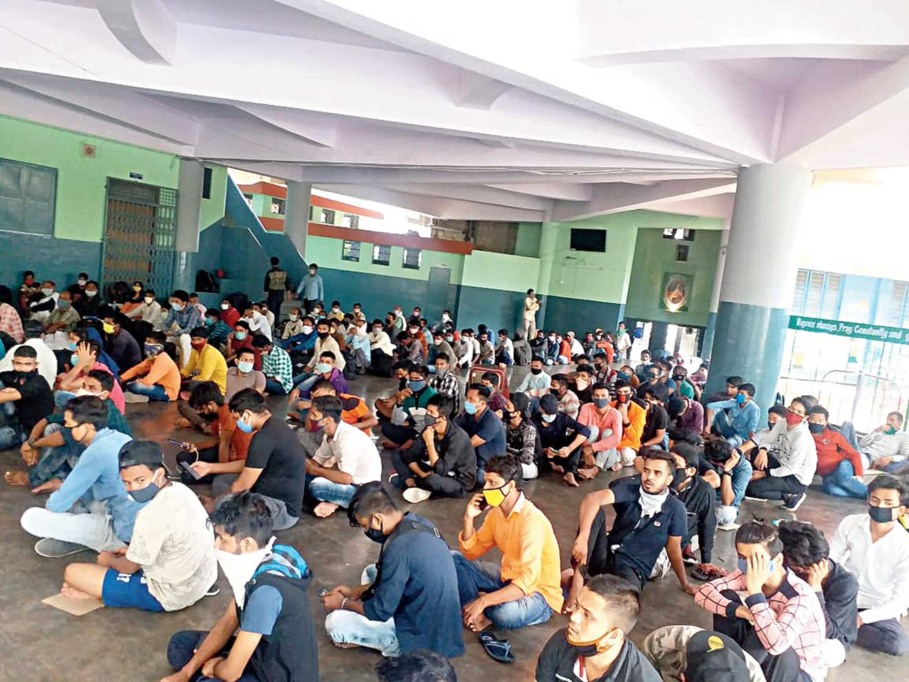 Migrant workers at a shelter in Bangalore on Friday wait for their turn to return home
