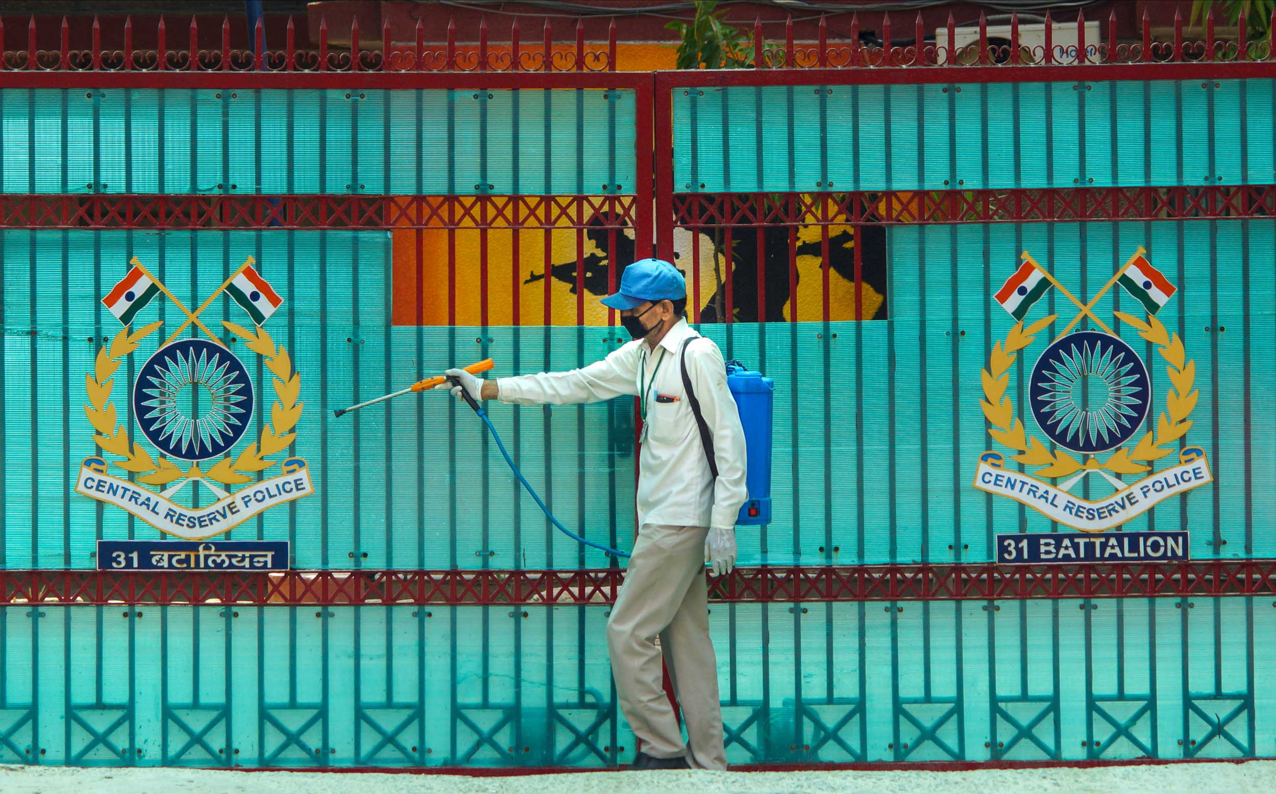 A municipal worker sprays disinfectants outside the CRPF 31st Battalian building in New Delhi on Saturday.