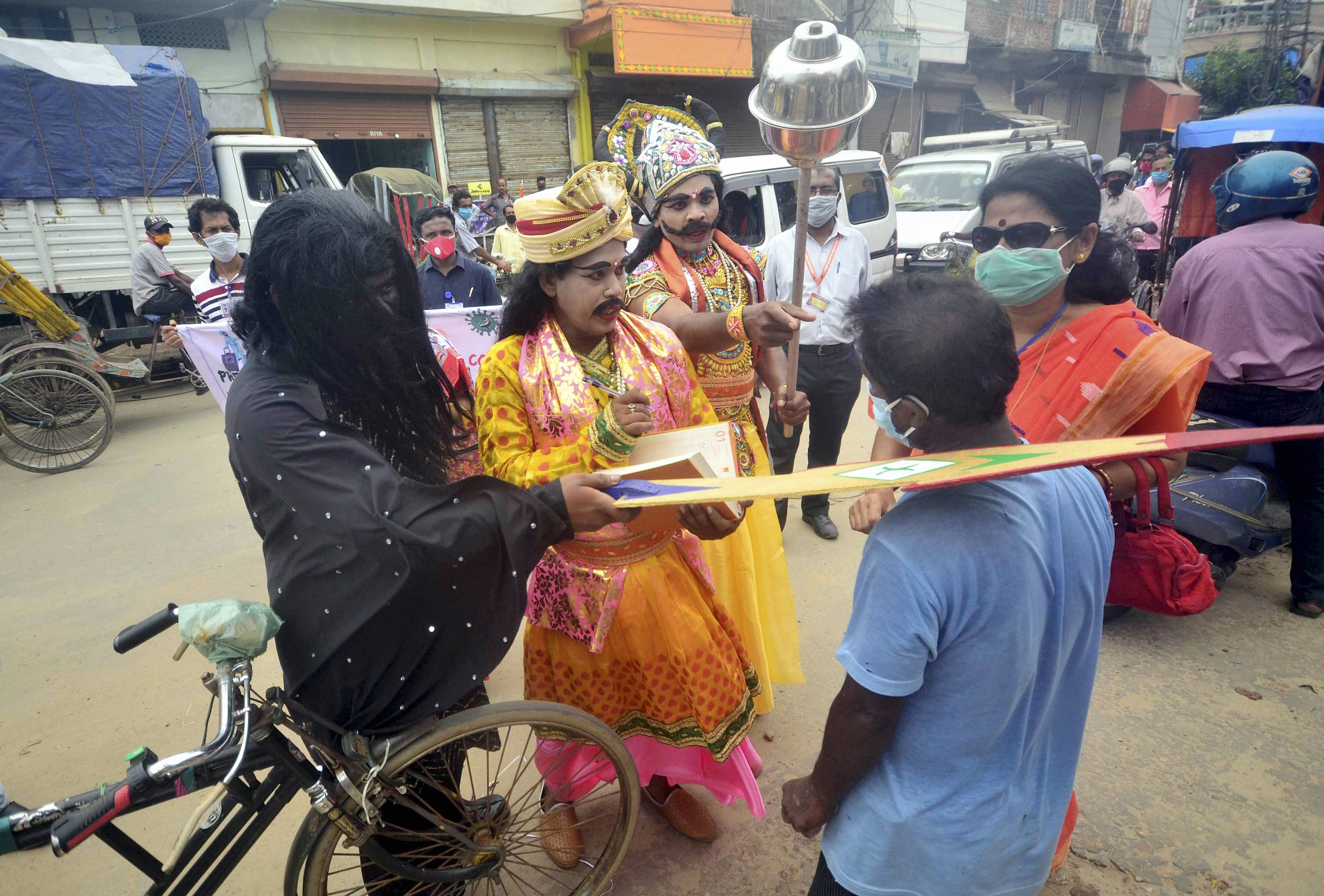 NGO volunteers distribute face masks while making people aware against Covid-19 on a road, in Agartala, May 22, 2020.