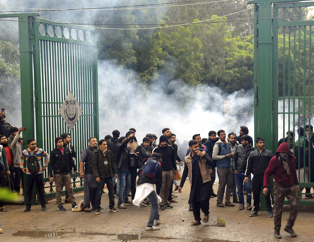 Police use tear gas to disperse students protesting outside Jamia Millia Islamia University against the Citizenship Amendment Act in New Delhi on Friday, December 13, 2019